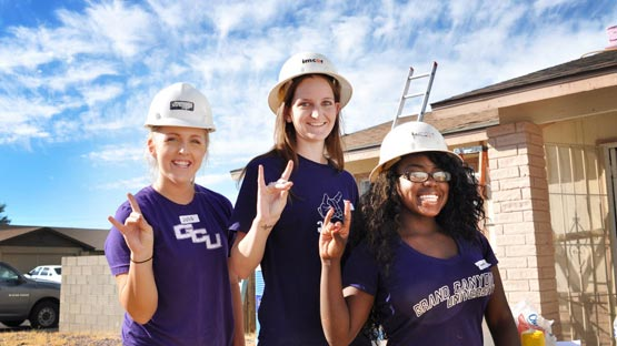 three female GCU students on site for Habitat for Humanity community home renovation